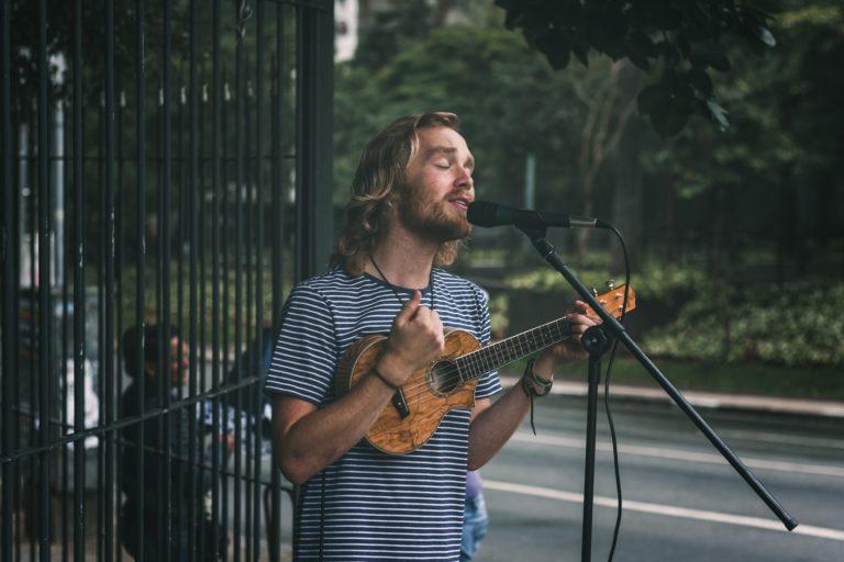 chico cantando y tocando el ukelele en la calle