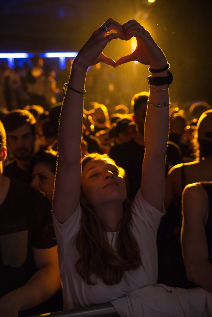 chica en un concierto con las manos en forma de corazón