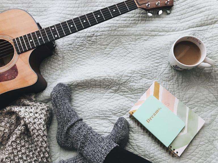 guitarra libre y café encima de la cama
