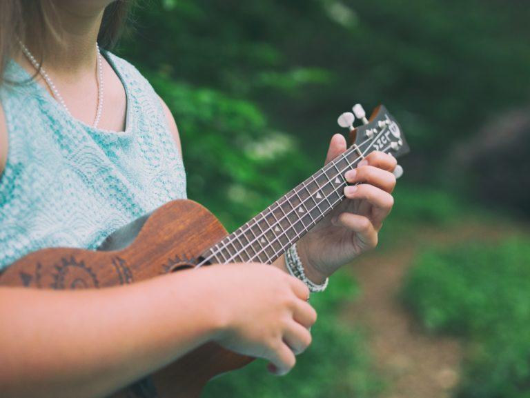 chica tocando la guitarra en el aire libre