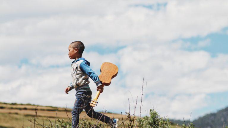 niño corriendo con una guitarra