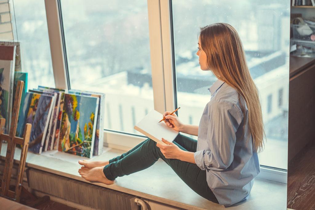 chica toma notas mirando sus cuadros