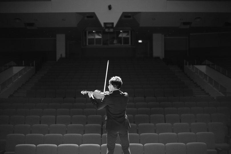 violinista tocando en un salón de actos